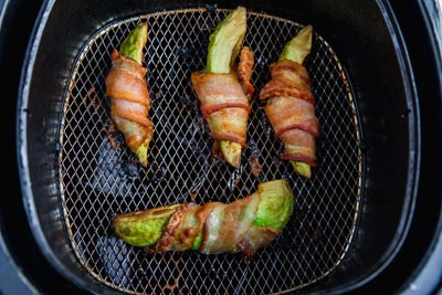 cooked bacon wrapped avocoado in an air fryer basket