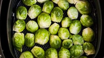 fresh brussels sprouts cut side down in the air fryer basket