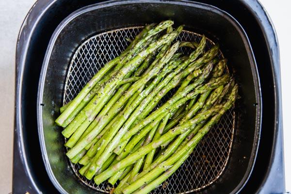 asparagus spears in an air fryer basket