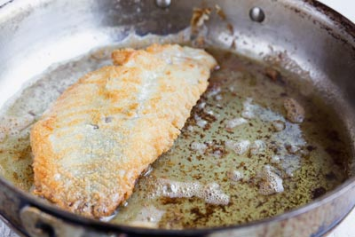 fried rockfish fillet frying in a skillet with hot oil