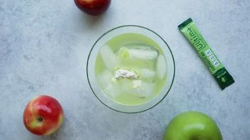 ingredients for a green drink in a glass with two apples next to the glass