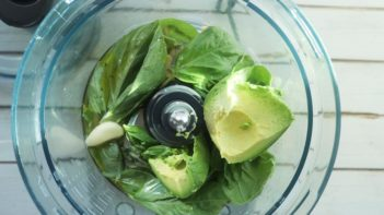 chunks of avocado on a bed of basil leaves in a food processor