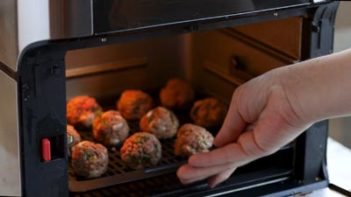 placing a tray of meatballs in the air fryer