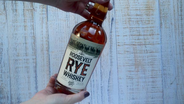 holding a bottle of rye whiskey