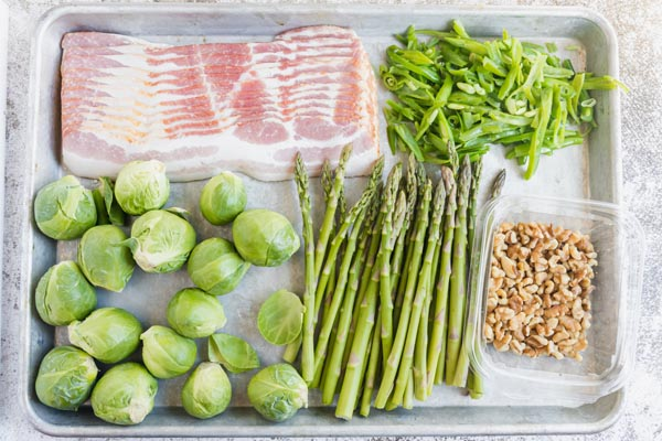 ingredients like asparagus, brussels sprouts, green beans, walnuts and bacon for a sheet pan recipe on a tray