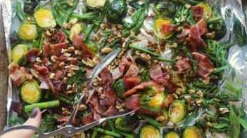 tossing the dressing over the bacon and brussels sprout salad