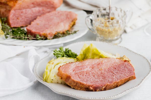 a slice of corned beef and cabbage on a dinner plate with mustard in a jar