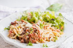 noodles and pasta sauce on a plate with parsley sprinkled and salad in the background