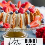 bundt cake dripping in white chocolate and topped with berries on a cake stand