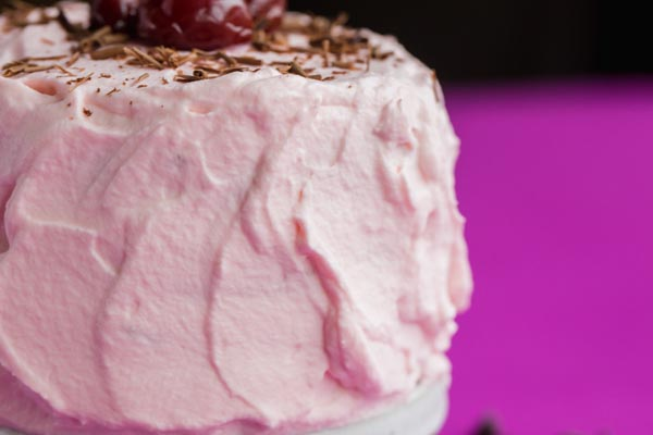 a thick layer of pink frosting on a cake