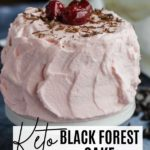 a small cake with pink frosting, shaved chocolate and cherries on top