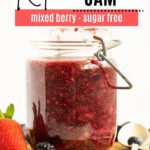 a big jar of mixed berry jam next to a spoon and a couple of berries