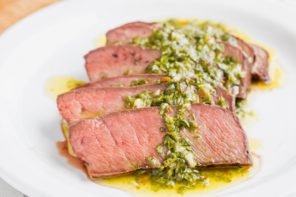 chopped herbs in oil cover slices of beef steak