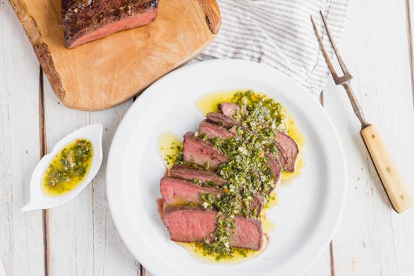 a plate of steak covered in chimichurri sauce with a fork and more steak nearby