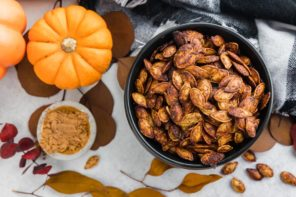pumpkin seeds in a black bowl next to chocolate powder and an orange pumpkin