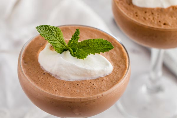 two frozen hot chocolate drinks with a dollop of whipped cream and a sprig of mint