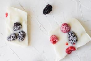two pieces of yogurt bark topped with berries
