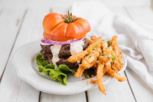 bunless burger with a tomato on top next to a mound of garlic parmesan jicama fries