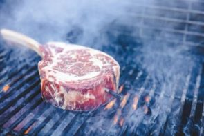 tomahawk steak on a grill over the flames with a meat thermometer stuck inside the meat