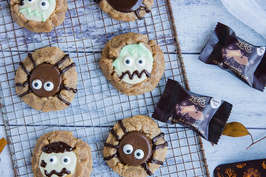 a wire rack with keto peanut butter cup cookies on it decorated like spiders and zombies