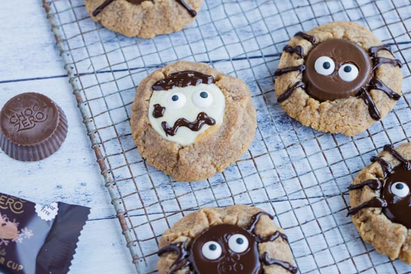 peanut butter cup cookies decorated like spiders and creepy zombies