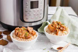 two bowls of keto sesame chicken sauce over cauliflower rice