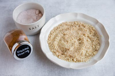 almond flour in a bowl with salt and cajun seasoning next to it