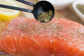 sprinkling italian seasoning on salmon