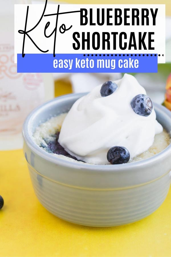 whipped cream and berries on top of a mug cake