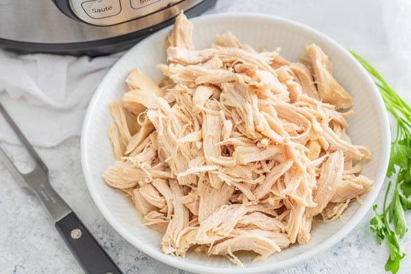 a bunch of shredded chicken in a white bowl next to an instant pot