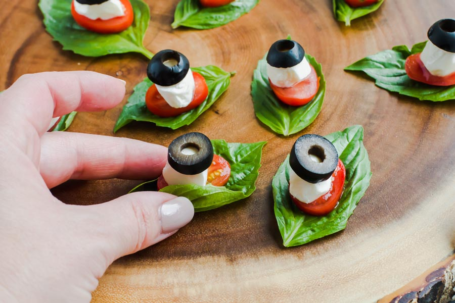 hand picking up a low carb caprese bite