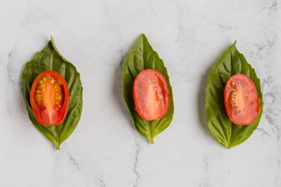 tomato slice on top of basil leaves