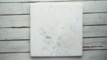 a square white marble slab on a wooden board