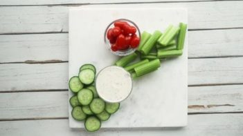 cucumber, celery, tomatoes and ranch dressing scattered on a marble board