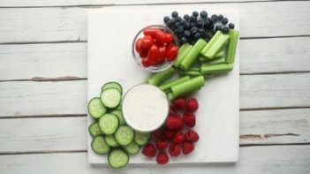 fresh vegetables and fruits on a white board