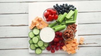 celery, cucumbers, berries on cheese on a marble board