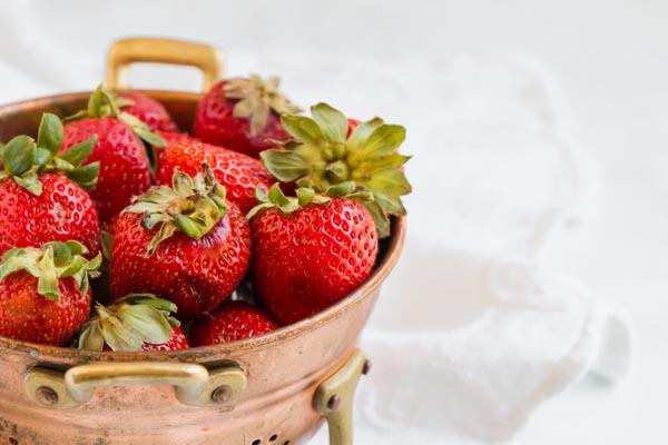 ripe strawberries in a copper collander