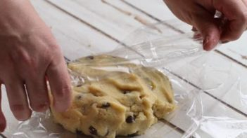 wrapping chocolate chip cookie dough with plastic wrap
