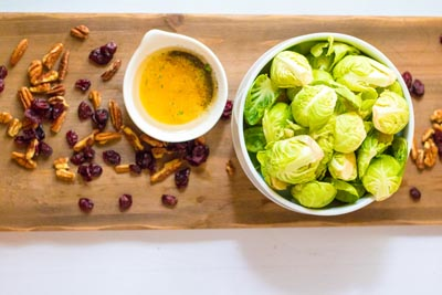 brussels sprouts and cranberries in a bowl with a sauce nearby