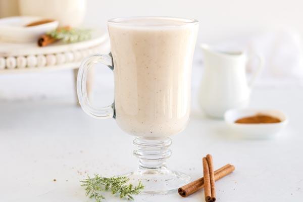 tall mug of eggnog with a cinnamon stick