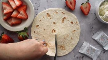 cutting a slit down the middle of a tortilla with scissors