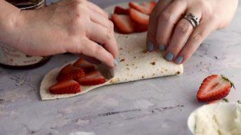 folding the tortilla over itself to make a wrap