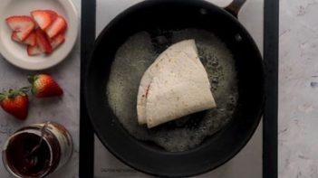 frying tortilla wrap in butter in a non-stick skillet