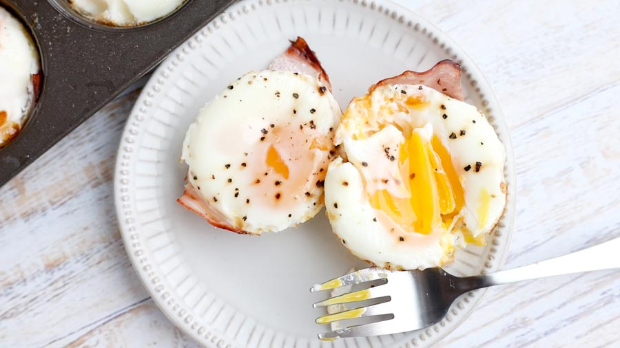 poached egg cut into with a fork to show creamy egg yolk