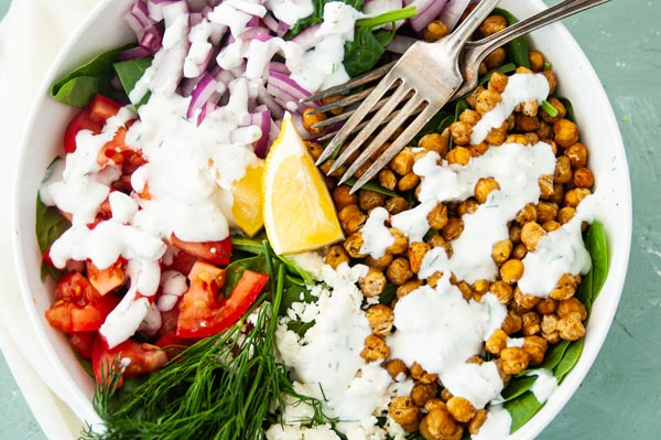 a colorful salad with tomato, dill and salad dressing on it