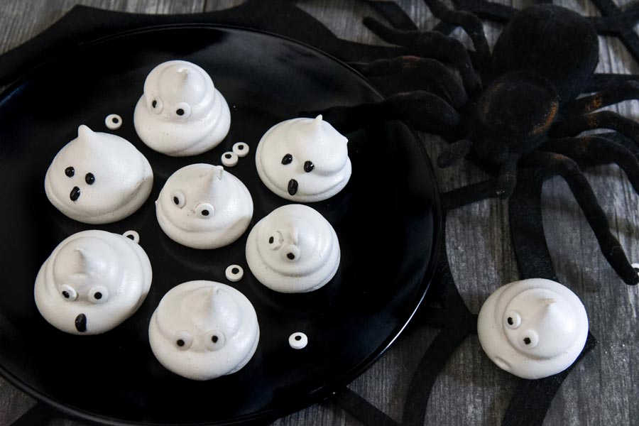 a plate with ghosts with candy eyes next to a spider