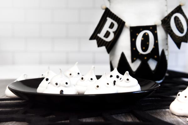 a bunch of white ghosts on a plate with a boo banner in the background