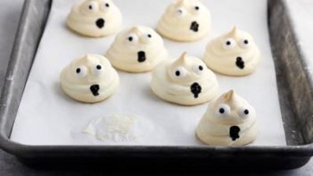 a baking tray with ghost cookies on it
