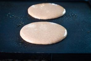 keto gingerbread pancakes cooking on a griddle