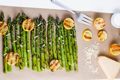 grilled asparagus on a sheet of parchment paper with lemons and parmesan cheese